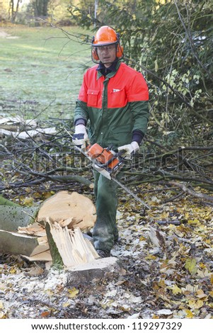 man cutting firewood for home with a chainsaw. wearing protective clothes for safety. - stock photo