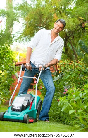 Man cutting green grass at home in tropical garden - stock photo