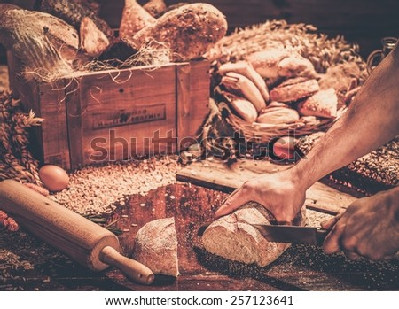 Man cutting homemade bread  on a table - stock photo