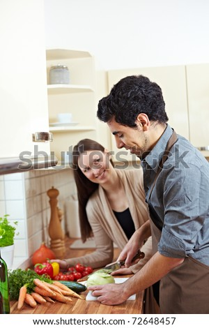 Man cutting kohlrabi in kitchen while woman is watching him - stock photo