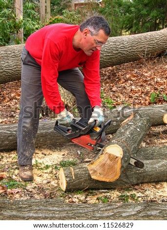 Man cutting log into sections with chainsaw - stock photo