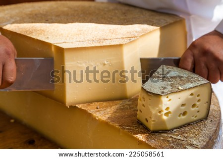 Man cutting piece of cheese - stock photo
