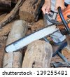 Man cutting piece of wood with chain saw. - stock photo