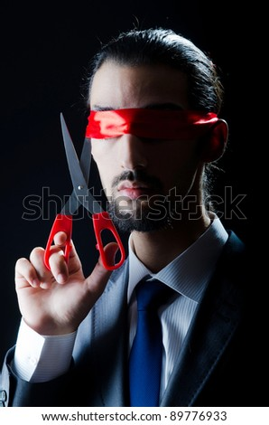 Man cutting ribbon on his eyes - stock photo