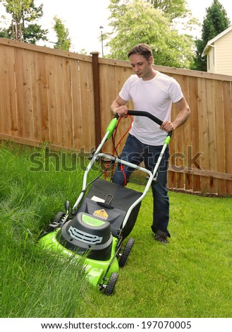 Man cutting the grass with lawn mower - stock photo