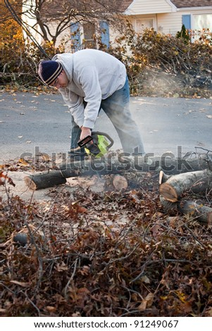 Man cutting tree limbs with a chainsaw that have fallen from storm damage.  A late fall snow storm in the month of October was the cause. - stock photo
