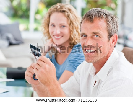 Man cutting up his credit card at home