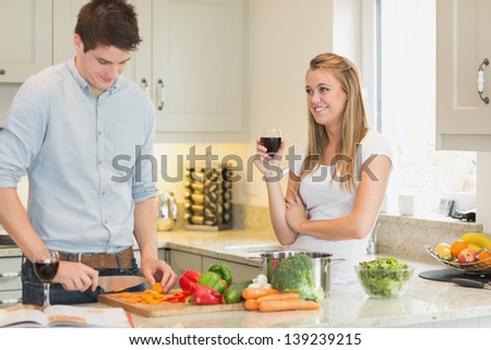 Man cutting vegetables with woman drinking wine in kitchen - stock photo