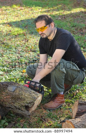 Man cutting wood with electric saw