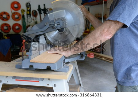 Man Cutting Wood with Table Saw - stock photo