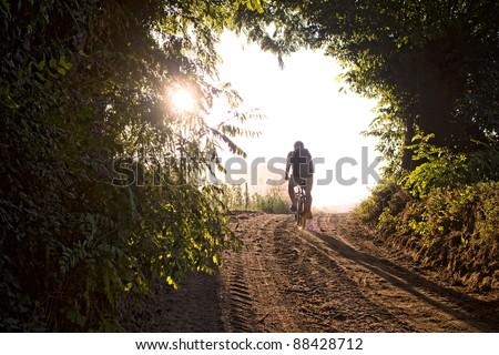 Man cycling on mountain bike along country trail - stock photo