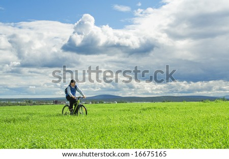 Man cycling through the meadow in the countryside - stock photo