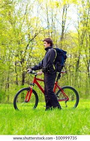 Man Cyclist with Bike and Backpack against the background of green nature in spring - stock photo