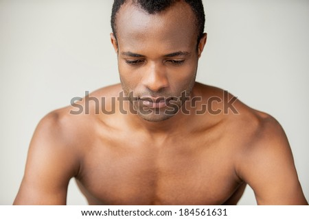 Man day dreaming. Handsome young muscular man looking down while standing against grey background - stock photo