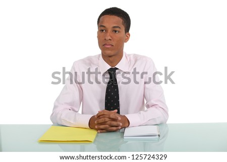 Man daydreaming whilst sat at his desk - stock photo