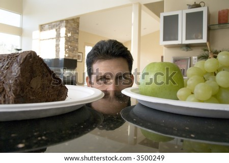 Man decides between cake and grapes - stock photo