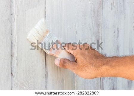 man decorating or painting with a paint brush - stock photo