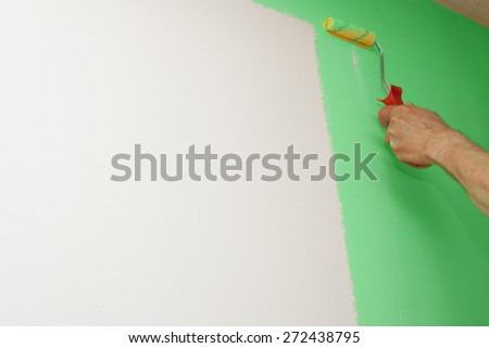 Man decorating or painting with a paint brush. Man painting wall. Brush in hand on color background with some space for Your text.  - stock photo