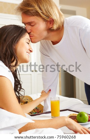 Man delivering breakfast on the tray to her spouse on bed in the morning