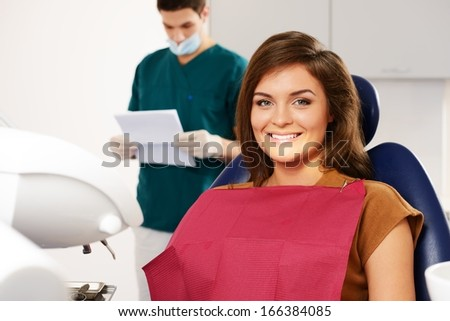 Man dentist reading woman patient's card - stock photo
