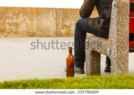 Man depressed with wine bottle sitting on bench outdoor. People abuse and alcoholism problems. - stock photo