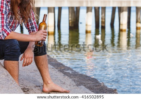 Man depressed with wine bottle sitting on sea shore outdoor. People abuse and alcoholism problems - stock photo