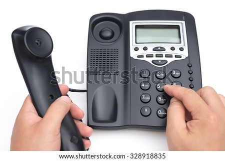 man dialing a black telephone on a white background - stock photo