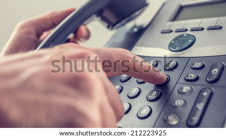Man dialling out on a landline telephone pressing the number 6 with his finger on the keypad in a communications concept, close up of his hand and the instrument. With retro filter effect. - stock photo