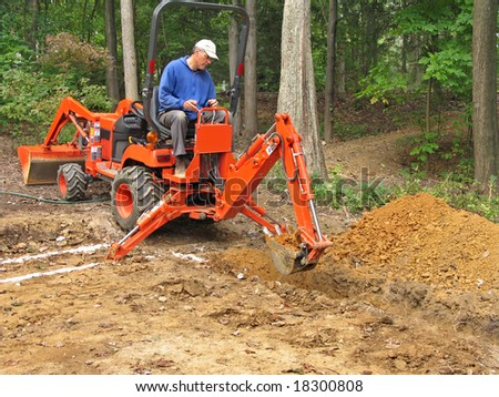 Man digging foundation trench with backhoe - stock photo