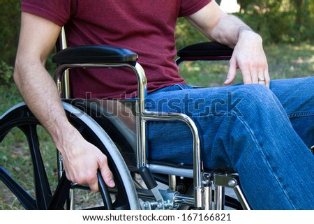 Man disabled by an accident sits in a wheelchair outside. - stock photo
