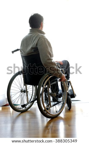 man disabled sitting in a wheelchair in the room in front of the window