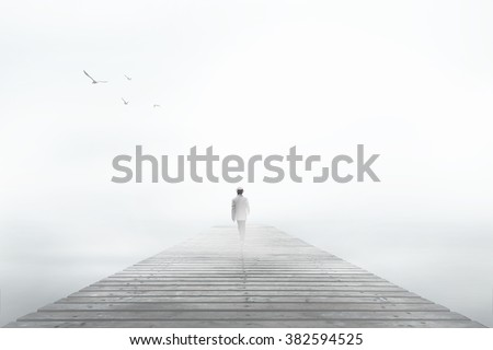 Man disappearing in the white fog - stock photo