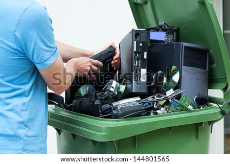 Man discarding old electronics int the plastic bin - stock photo