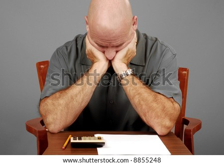 Man distressed going over numbers with calculator - stock photo
