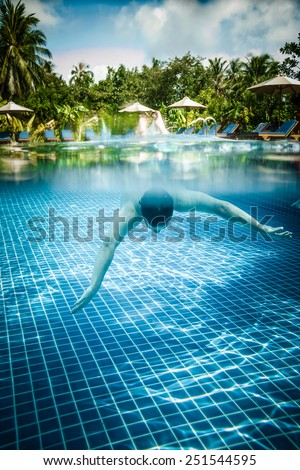 Man dives into a swimming pool views over the water and under water. Maldives. - stock photo