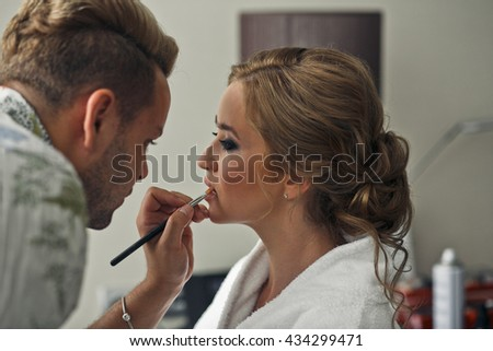 MAn does a make-up for a pretty blonde lady - stock photo
