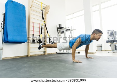 Man does crossfit push ups with trx fitness straps in the gym's studio - stock photo