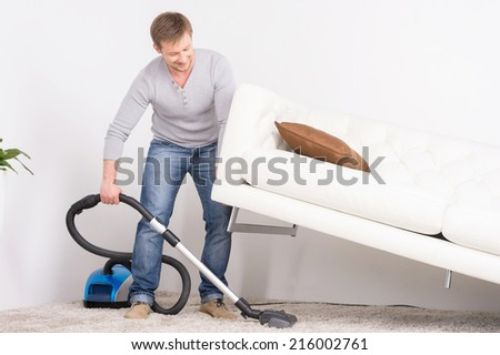 man does house work with vacuum cleaner. Men lifted sofa in living room, vacuum cleaning.  - stock photo