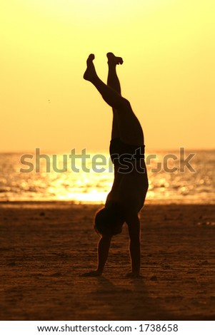 Man doing a handstand in the beach