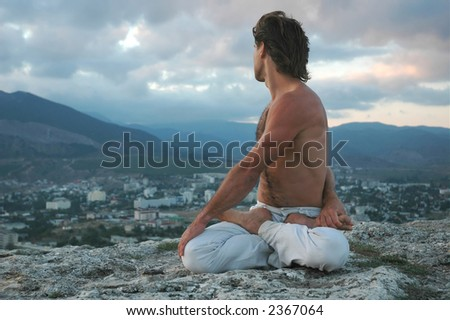 Man doing a padmasana - lotus posture (variant) - stock photo