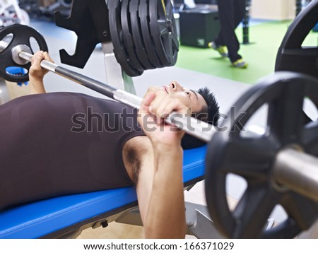 man doing bench press in gym. - stock photo