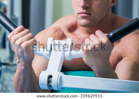 Man doing biceps on the bench trainer at the gym. The power to exercise the muscles of hands. Heavy training young athlete. Photos for sporting magazines, posters and websites. - stock photo