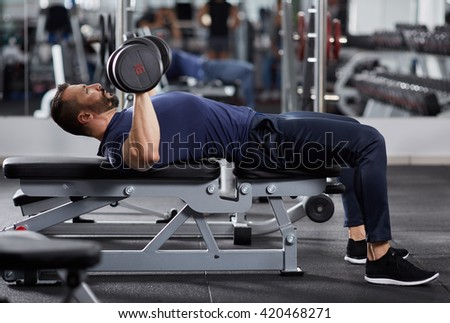 Man doing chest workout, bench press with dumbbells - stock photo