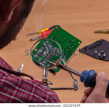 Man doing close-up of Soldering work