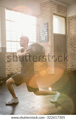 Man doing exercise with medicine ball at the gym - stock photo