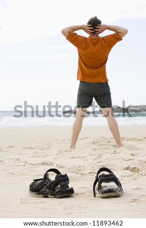Man doing exercises on a beach in summer - stock photo
