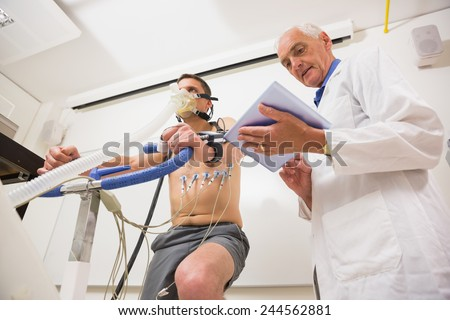 Man doing fitness test on exercise bike at the medical centre - stock photo