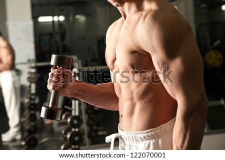 man doing fitness with weights in a gym - stock photo
