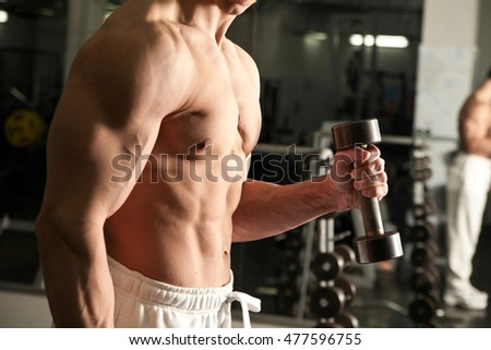 man doing fitness with weights in a gym