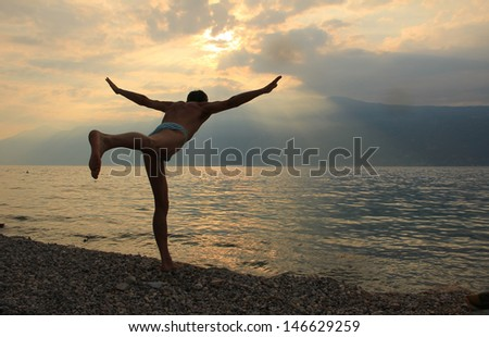 man doing gymnastics in the morning at the lakeside - stock photo